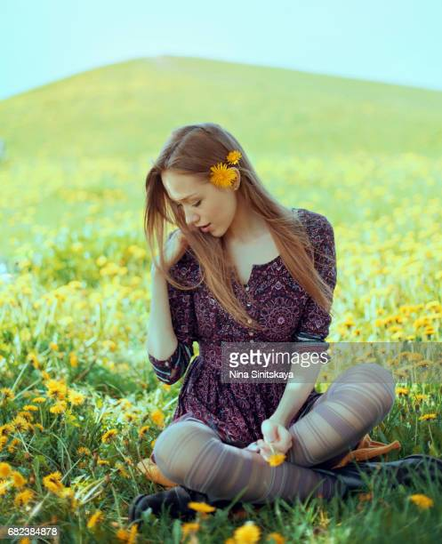 Attractive woman sitting among dandelion flowers on meadow