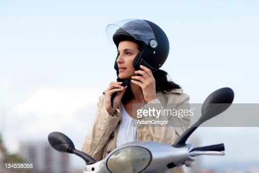 Attractive woman takes off her helmet : Stock Photo
