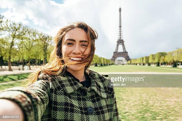 Belle femme prenant un selfie devant le tour Eiffel