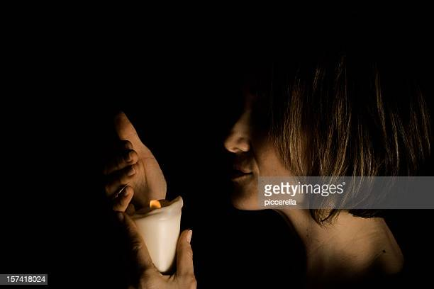 Attractive woman turning off a candle