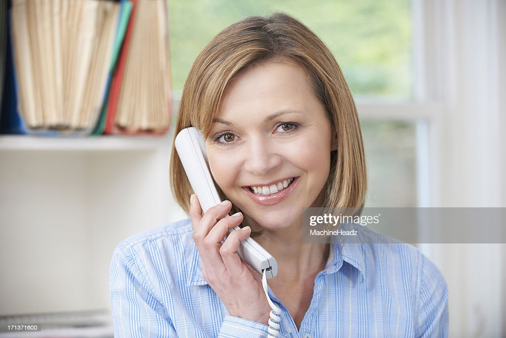 Attractive Woman Using Telephone In Home Office