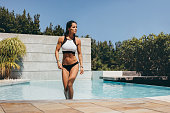 Shot of attractive young woman walking out of swimming pool. Healthy female model in swimwear stepping out of the pool and looking away.