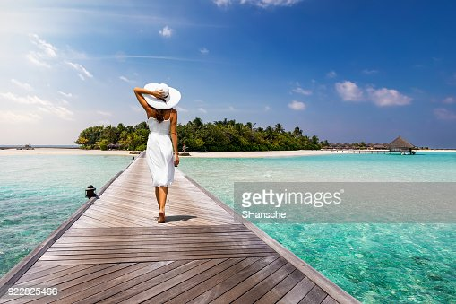 Attractive woman walks over a wooden jetty towards a tropical island : Stock Photo