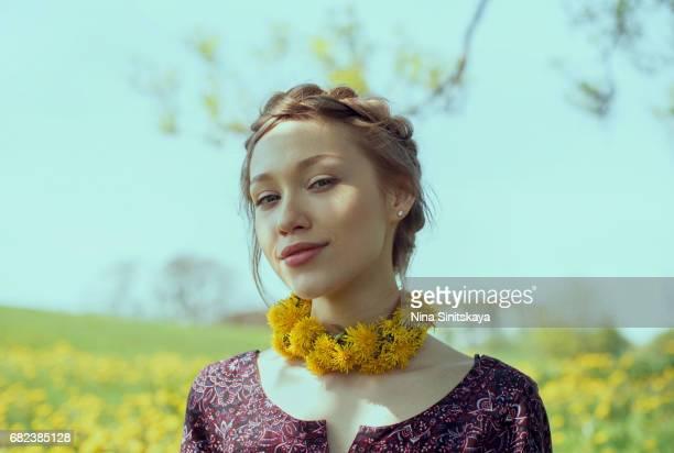 Attractive woman wears dandelion choker in dandelion field