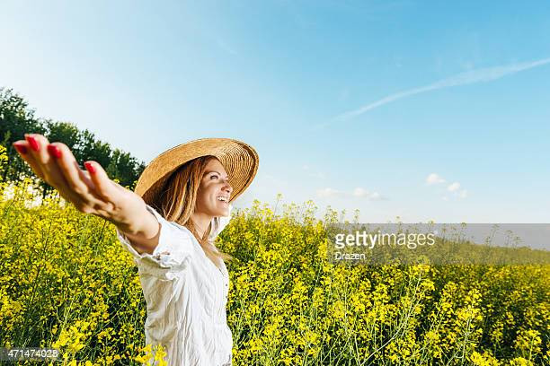 Attractive woman with outstretched arms in rapeseed field in summer