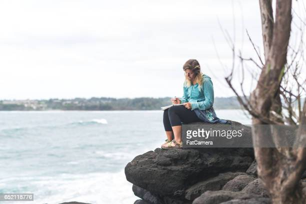 Attractive woman writing in journal on rock outcropping over Hawaiian coastline