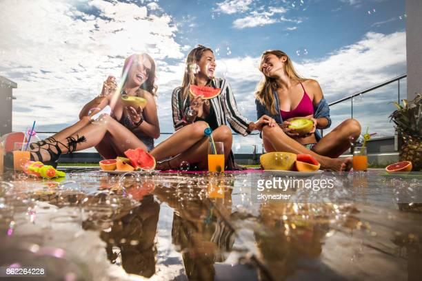 Jolies femmes manger des fruits et le commérage au cours de la journée d'été sur une terrasse.
