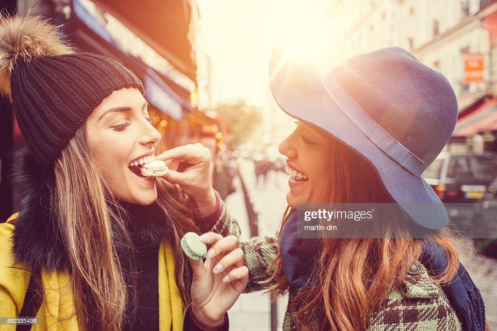 Attraktive Frauen Essen Pariser Makronen : Stock-Foto