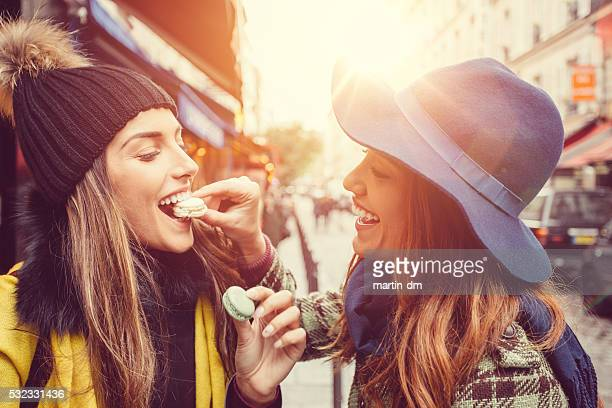 Attractive women eating parisian macaroons