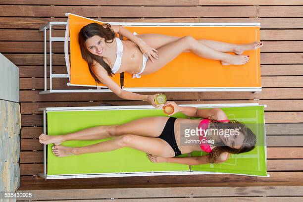 Attractive Women In Bikinis on Sun loungers
