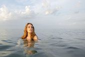 Attractive woman stares off in the distance as she wades in a large body of water.