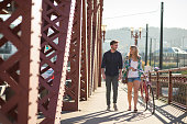 Attractive young adult couple walking and riding a
