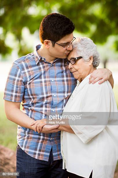 Attractive young adult man embracing his grandmother