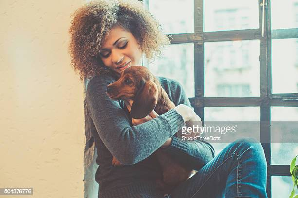 Mujer atractiva joven africana jugando con cachorro