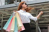 Attractive young Asian woman in casual clothes carrying colorful shopping bags outdoors
