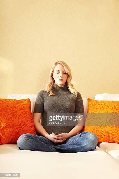 Attraktiven jungen blonden Frau Meditieren auf Ihrem Sofa