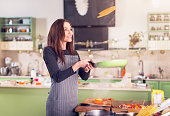 Attractive young brunette housewife in casual clothes and apron tossing pancakes on pan in the kitchen.