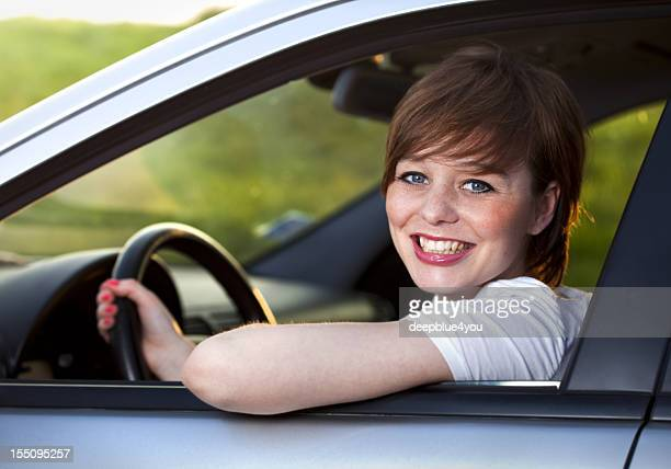 Attractive young brunette woman in her car