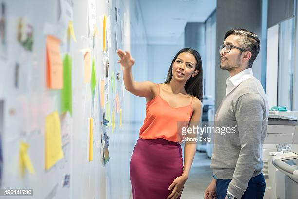 Attractive young businesswoman discussing with male colleague