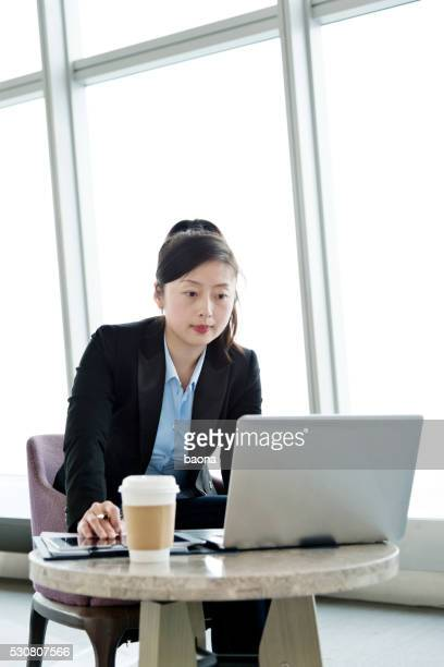 Attractive young businesswoman using laptop at a cafe