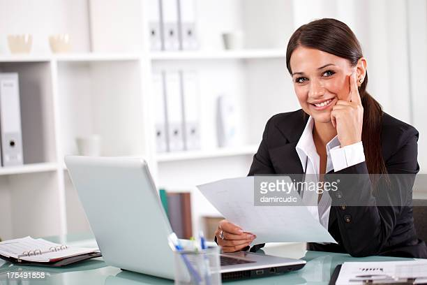 Attractive young businesswoman working on documents in office