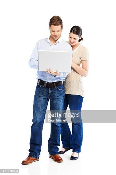 Attractive young couple using laptop on white