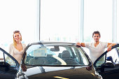 'Attractive, young couple with their new car at showroom'