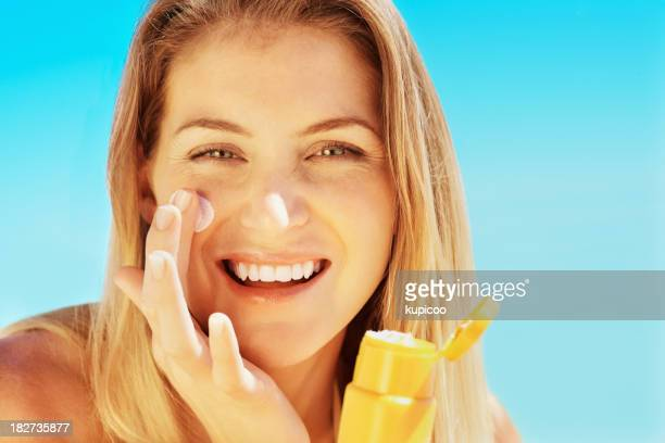 Attractive young female applying sunscreen to face