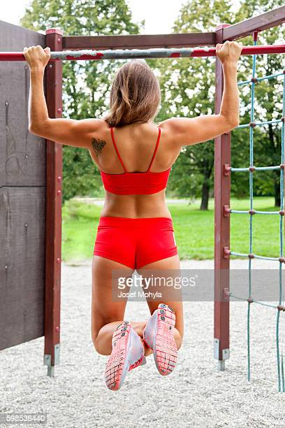 Attractive young female bodybuilder practicing outdoor on horizontal bar