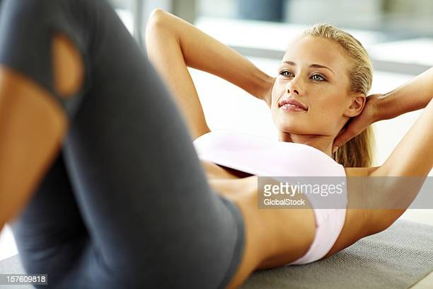 Attractive young female doing stomach crunches