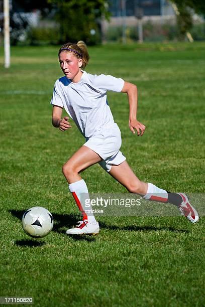 Atractiva joven mujer jugador de fútbol de perfil Dribble contacto