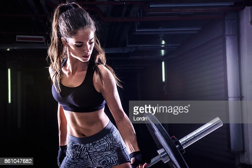 Attractive young fit sportswoman working out with weights : Stock Photo
