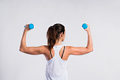 Attractive young fitness woman in white singlet, working out with dumbbells. Rear view. Studio shot on gray background.