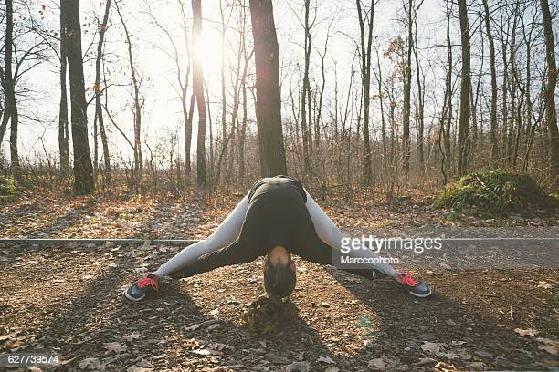 Attractive young girl exercising outdoors, bending, stretching on the ground