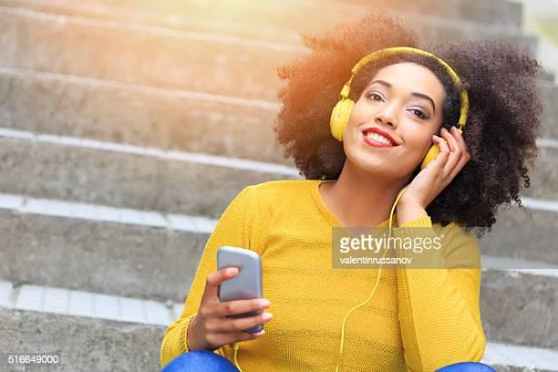 Jolie jeune fille écoutant de la musique assis sur les escaliers