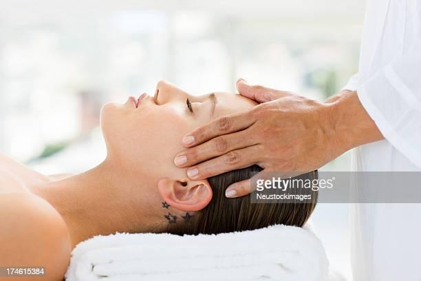 Attraente giovane ragazza ricevendo il massaggio alla testa spa