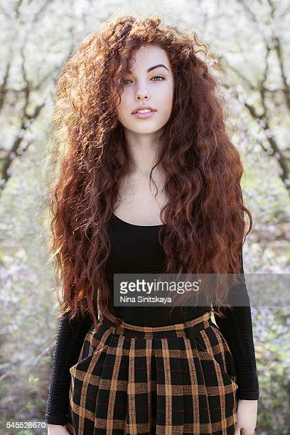 Attractive young girl with long brown curly hair standing in bloom