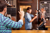 Cheerful man is ordering beer in bar. He is sitting at counter and gesturing to barman. The worker is standing and pouring taping beer carefully