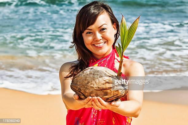 Attraktive junge Frau auf Hawaii am Strand mit Kokos Setzling