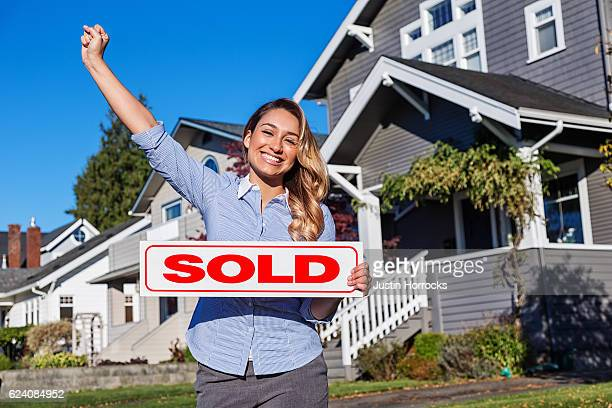 Attractive Young Hispanic Realtor with SOLD Sign