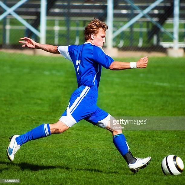 Attractive Young Male Soccer Player Sprints into Ball Kick