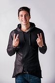 Attractive young man doing peace or victory sign with two fingers, on white
