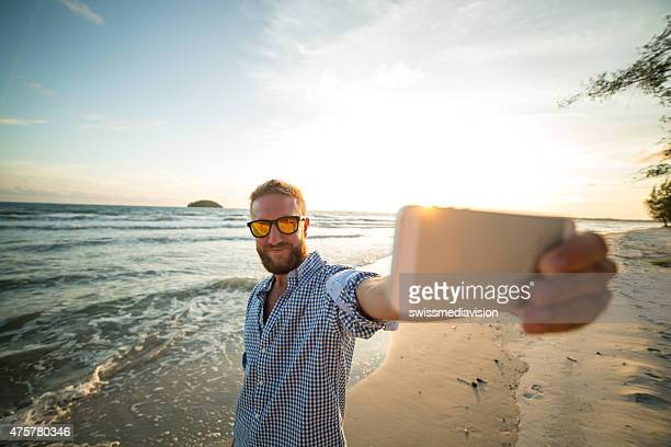Attractive young man on the beach taking selfie