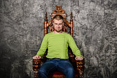Attractive young man in a light green t-shirt sitting on the throne and smiling looking at the camera