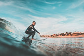 Handsome young man rides a wave off the coast with his surfboard. Extreme water sports and outdoor active lifestyle. Vintage filter with soft style