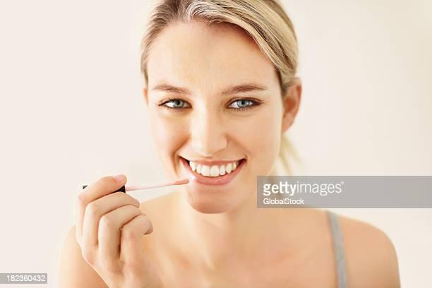 Attraktive junge Frau benutzt Lipgloss