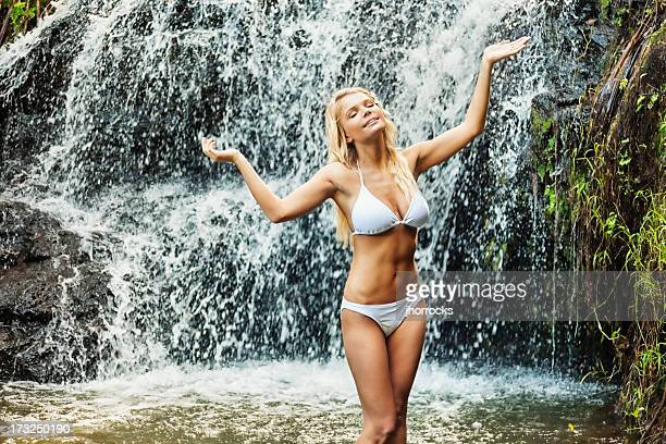 Attractive Young Woman Cooling Off Under Waterfall