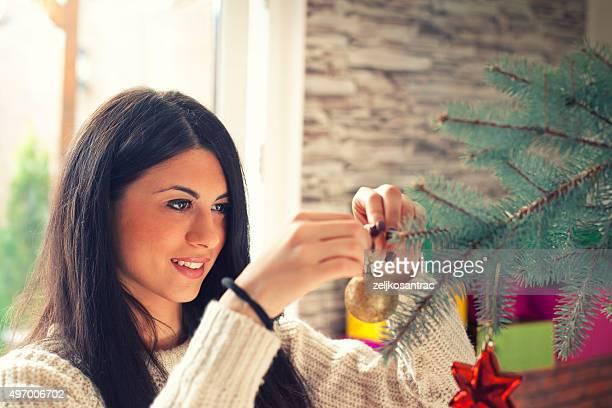 Attraente giovane donna Decorare l'albero di Natale