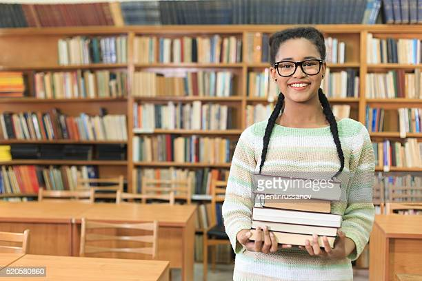 Attractive young woman holding stack of books in the library