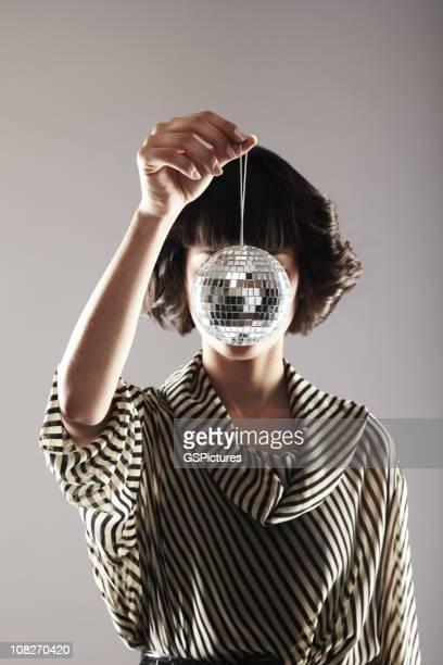 Attraktive junge Frau hält eine Disco Ball